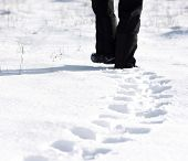 stock photo of black pants  - Person wearing black pants walking in the snow and leaving footprints - JPG