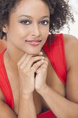 image of settee  - A beautiful mixed race African American girl or young woman wearing a red dress looking happy and smiling - JPG