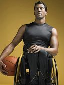 Portrait of a confident paraplegic athlete in wheelchair holding basketball against yellow backgroun