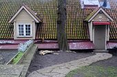 image of gabled dormer window  - Part of the house with attic entrance and old tiled roof in Tallinn in Estonia - JPG