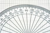 stock photo of protractor  - detail of plastic protractor over graph paper - JPG