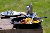 stock photo of scrambled eggs  - Cast iron frying pan full of eggs, beef and bacon at a Civil War re-enactment