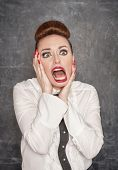 image of grotesque  - Scared teacher in white blouse on the blackboard background - JPG