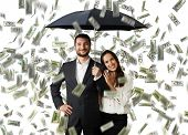 image of lottery winners  - young smiley couple with black umbrella standing under money rain - JPG