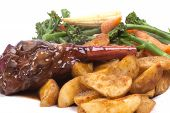 foto of lamb shanks  - Lamb Shank in a Rosemary and Red Wine Jus with vegetable on a white plate - JPG