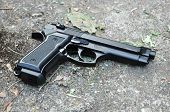 stock photo of 9mm  - A black 9mm gun on a ground - JPG