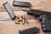 foto of pistols  - A 1911 45 caliber pistol with bullets - JPG