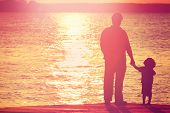 foto of dock a lake  - Father and son  on a dock at sunset - JPG
