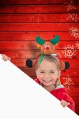 foto of rudolph  - Festive little girl showing poster against snowflake pattern on red planks - JPG