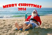 stock photo of christmas claus  - Santa Claus relaxing in his lounge chair on a tropical sandy beach  - JPG