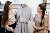 picture of showrooms  - Young woman choosing clothes on a rack in a showroom  - JPG