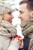 stock photo of amor  - Young amorous man giving small present to his girlfriend and both looking at one another - JPG