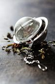 image of food chain  - Tea composition with tea strainer on dark background - JPG