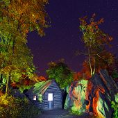 picture of log cabin  - Log cabin under the summer night sky with glowing stars above lit with green and red light  - JPG