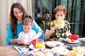 stock photo of family bonding  - Beautiful hispanic family having breakfast together on the outdoor dining showing family bonding time - JPG