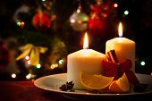 foto of cinnamon sticks  - Christmas decoration candles cinnamon sticks and pieces of orange on christmas tree background  - JPG