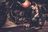 foto of carburetor  - Biker repairing his custom motorcycle bobber on a road  - JPG