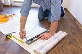 stock photo of handyman  - Handyman measuring wallpaper to cut - JPG