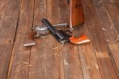 stock photo of revolver  - Two revolvers with bullets on a wooden background - JPG
