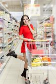 foto of local shop  - Portrait of a young girl in a market store with a shopping cart - JPG