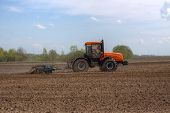 stock photo of plow  - Tractor with a cultivator plowing the field in the spring - JPG
