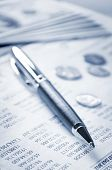 picture of statements  - A pen and US currency on the paper of statement - JPG