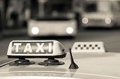 foto of headlight  - auto emblem and sign of a taxi against city streets with the vague image of buses and the included headlights of beige color - JPG
