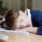 foto of diligent  - Diligent preschool sitting at desk classroom - JPG