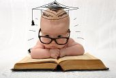 pic of cute innocent  - cute little baby in glasses with painted professor hat lieing on old book on light background - JPG