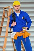 stock photo of  multimeter  - Electrician holding cables and multimeter against grey shutters - JPG