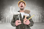 picture of scream  - Screaming manual worker holding various tools against hand drawn city plan - JPG