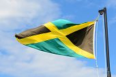picture of jamaican flag  - Flag of Jamaica waving against blue sky - JPG