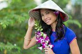 picture of conic  - Pretty Vietnamese woman wearing a traditional conical hat holding orchid flower bunch - JPG