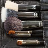 image of makeup artist  - Makeup brushes in a makeup artist belt - JPG