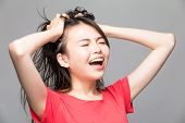 picture of pulling hair  - Frustrated and stressed angry Chinese woman pulling her hair with hands - JPG