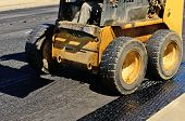 picture of skid-steer  - Small skid steer tractor moving asphalt on a repaving project - JPG