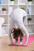 picture of bend  - Vertical view of stretched woman bending down - JPG