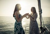 pic of life-boat  - two girls making a toast on the boat - JPG