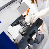 stock photo of fluorescent  - Scientist microscoping on hi - JPG