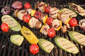 image of kababs  - Homemade Shish Kabobs BBQ with Meat Peppers Tomatoes and Mushroms With Grilled Vegetables Zucchine Eggplant and Onions on Hot Grill - JPG