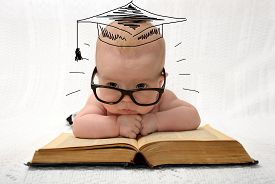 picture of professor  - cute little baby in glasses with painted professor hat lieing on old book on light background - JPG