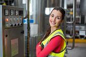 Portrait of female factory worker standing near machine in bottle factory poster