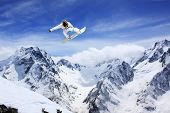 picture of gravity  - flying snowboarder on mountains - JPG