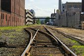 picture of train track  - railroad track switching station converging in the distance in cambridge massachusetts flanked by factory buildings - JPG