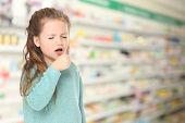 Allergies or cold concept. Little girl coughing at pharmacy poster