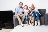 Smiling Family Sitting On Sofa And Watching Tv Together poster