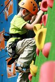 stock photo of climbing wall  - child climbing on a wall in an outdoor climbing center - JPG