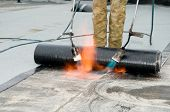 stock photo of roofs  - Roofing felt installation with heating and melting roll of bitumen roll by torch on flame - JPG