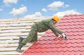 stock photo of girder  - worker on roof at screwdriving works with metal tile and roofing iron - JPG