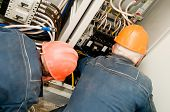 Two electrician man operating personnel installing and mounting new industrial wiring at voltage pan